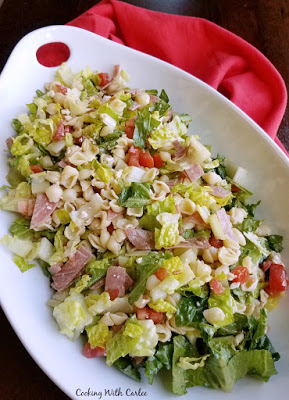 large platter of salad with pasta, cheese, meats, tomatoes etc.