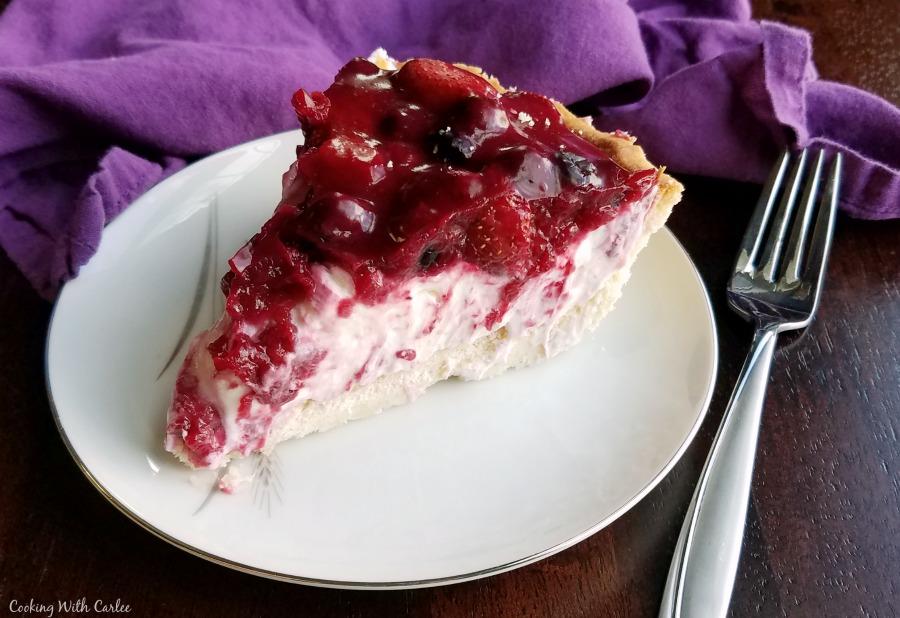 Slice of creamy lemon pie with berries on top.