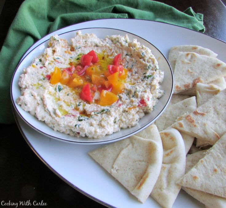 Bowl of Egyptian feta spread with herbs and tomatoes on platter with wedges of pita bread.
