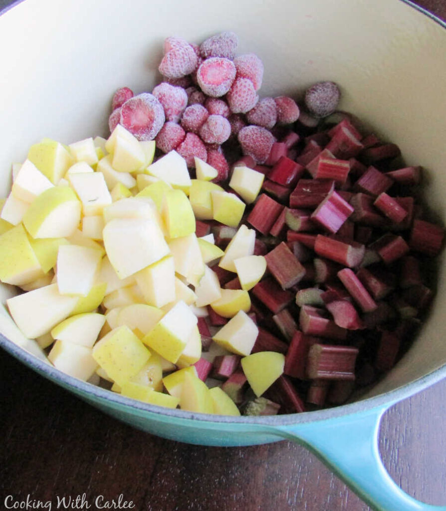 pot full of chopped apples and rhubarb and frozen strawberries.
