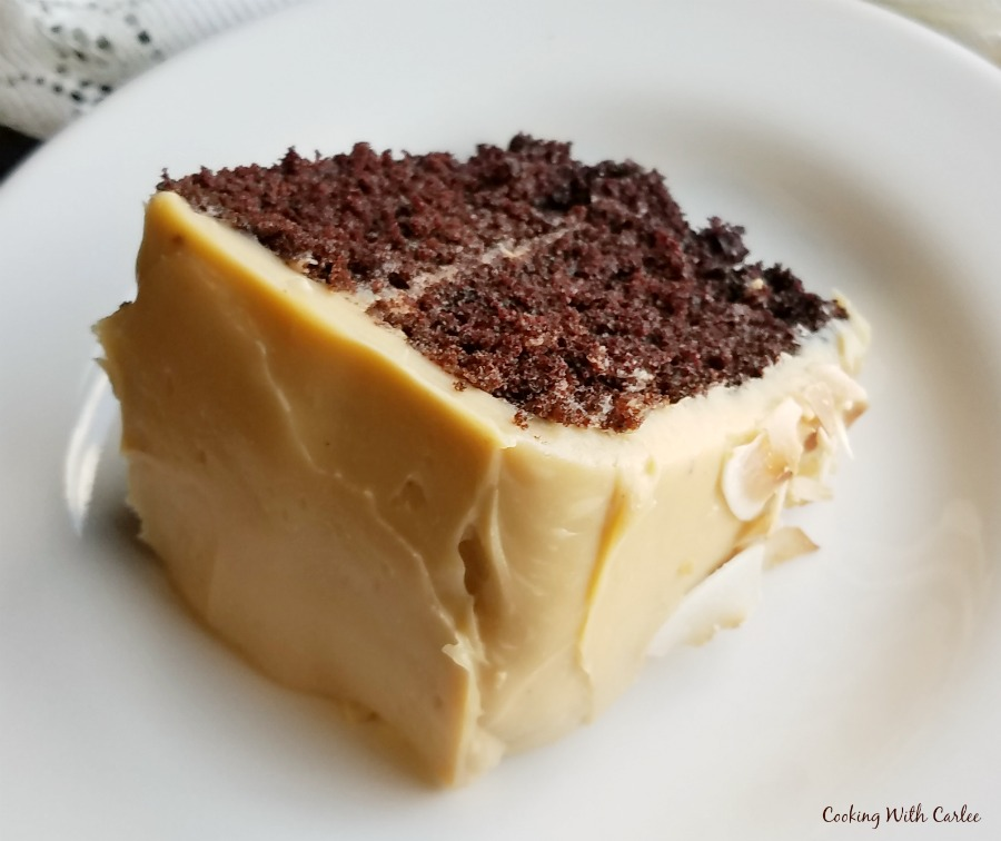 slice of layered chocolate cake with creamy caramel sweetened condensed milk frosting on it.