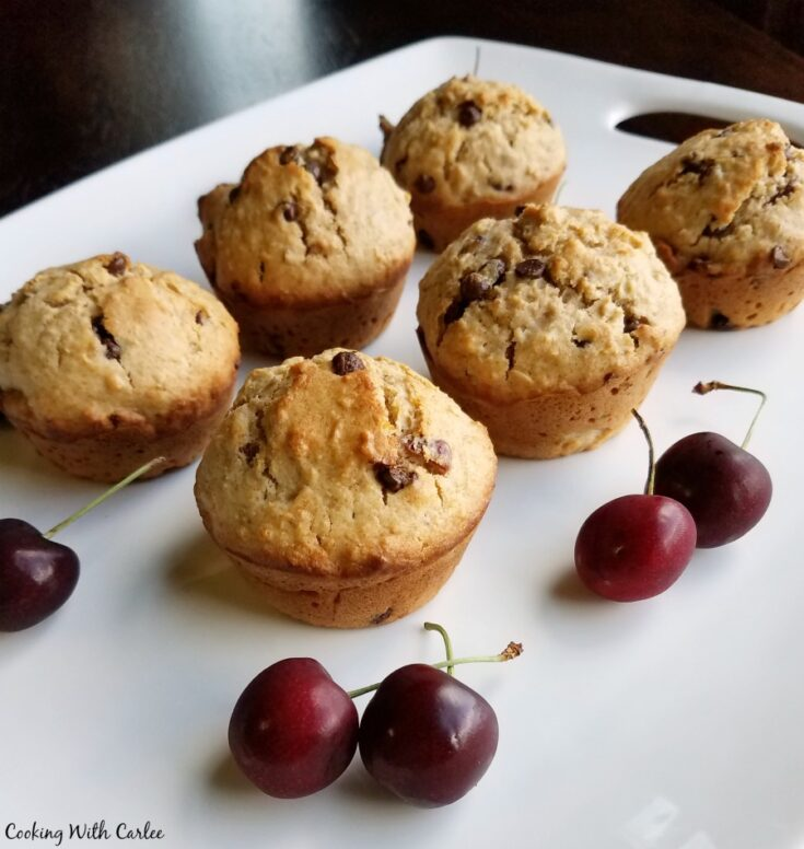 cherry chocolate chip oatmeal sourdough muffins on plate with fresh cherries.