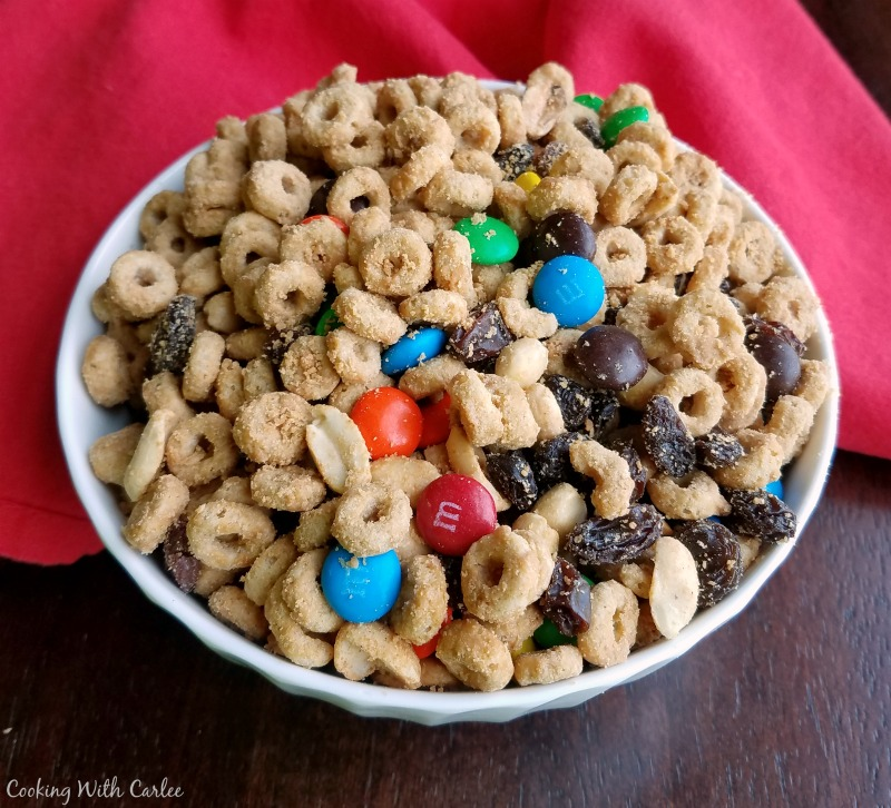bowl full of peanut butter maple coated cereal, candies. raisins and peanuts for snack mix