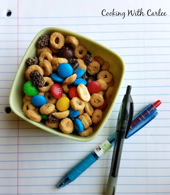 small container of peanut butter maple snack mix on a sheet of notebook paper with a couple of pens nearby as a perfect homework snack