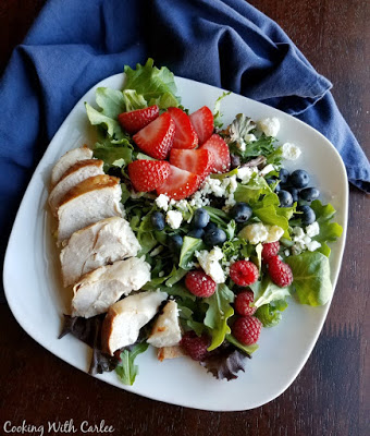 plate of greens with chicken breast, raspberries, strawberries, blueberries and crumbled cheese