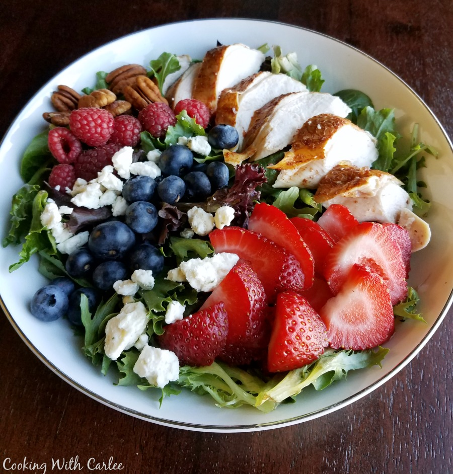 bowl of greens topped with berries, cheese, chicken and nuts
