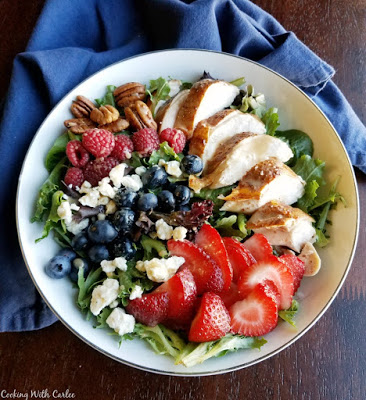 bowl of salad topped with fruit, cheese, nuts and more