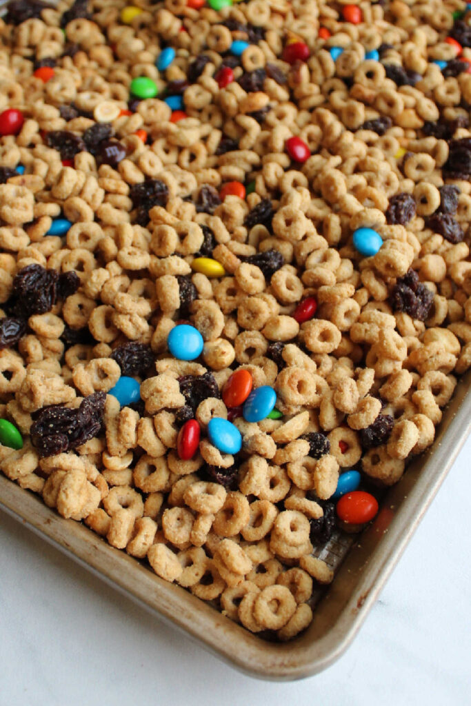 Sheet pan filled with trail mix style gorp snack mix with maple peanut butter coated cereal, candies, raisins and peanuts.