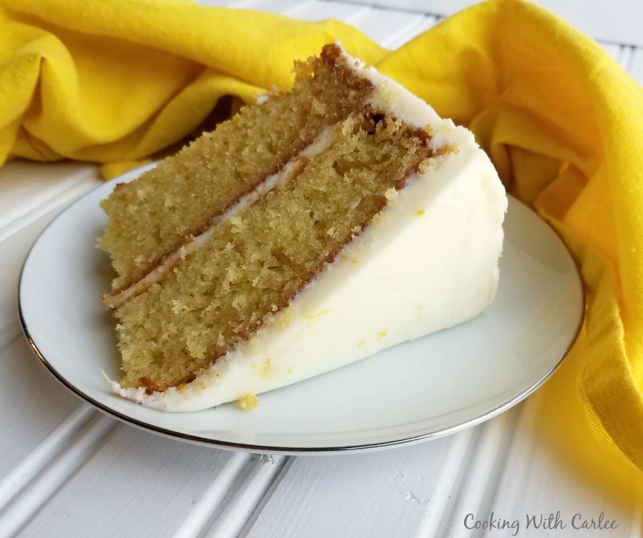 slice of layered lemon velvet cake with creamy lemon buttercream on outside.