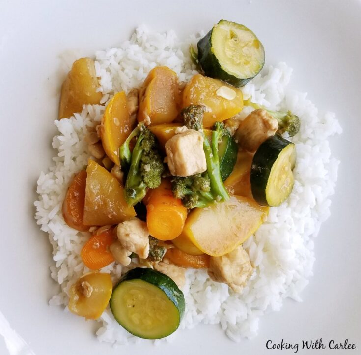 rice topped with chicken and veggie stir fry.