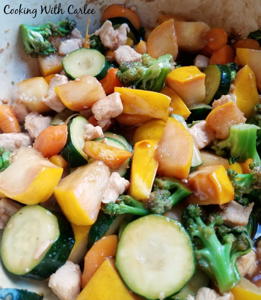 close up of chicken and veggies cooking in pan.