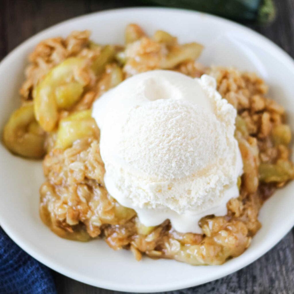 Plate of gooey zucchini zapple crisp with scoop of vanilla ice cream, ready to eat.
