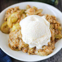 Plate of gooey zucchini zapple crisp with scoop of vanilla ice cream, ready to eat.