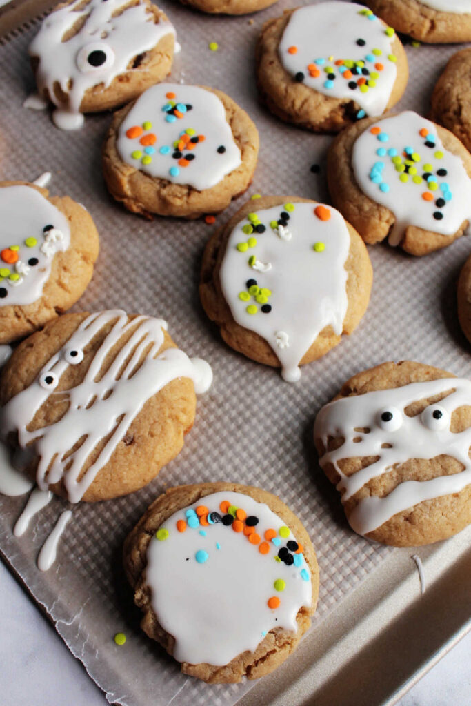 Tray of maple cinnamon cookies with white icing glaze and sprinkles on top.
