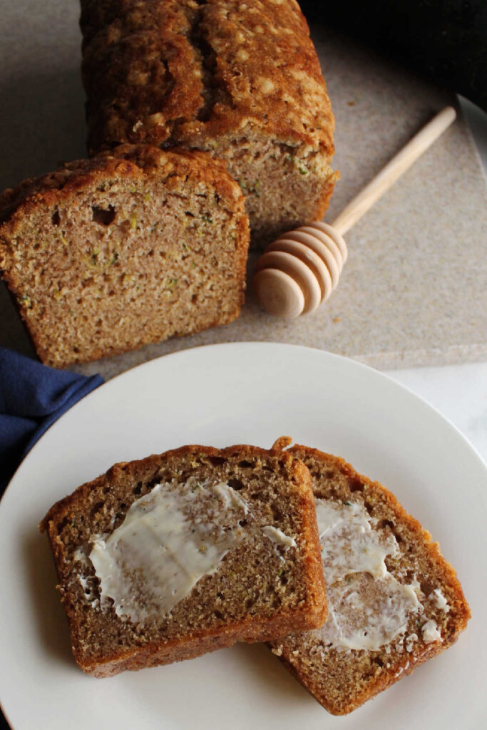Slices of zucchini bread with butter spread on slices.