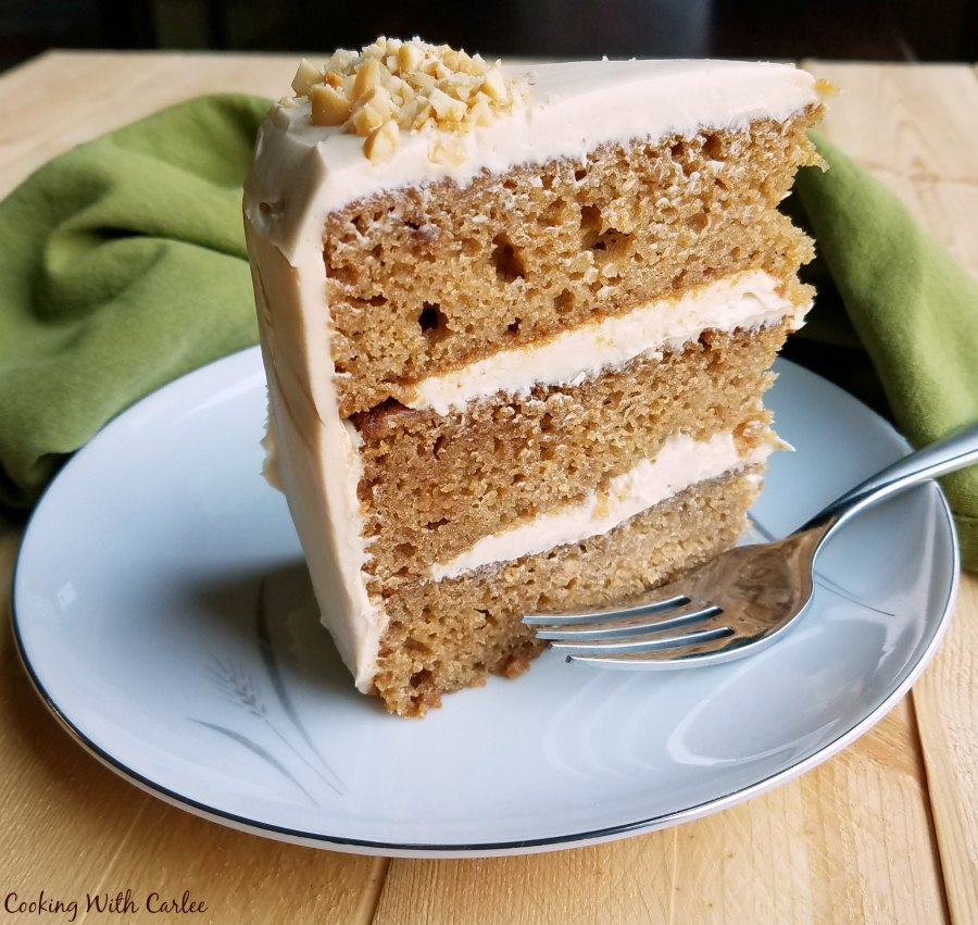 slice of applesauce cake with layers of soft caramel cream cheese frosting on dessert plate with fork.