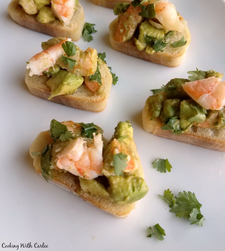 avocado and shrimp mixture on top of baguette slices with cilantro.