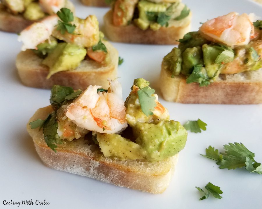 close up of baguette slices topped with avocado and shrimp mixture