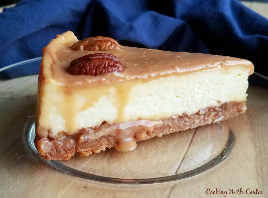 slice of cheesecake with caramel and pecans on top and layer of gooey caramel and pecans under cheesecake layer.