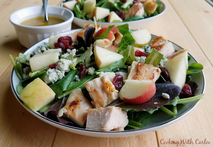 side view of bowls of fall dinner salad with chunks of apple, chicken, cranberries, cheese and homemade vinagriette.