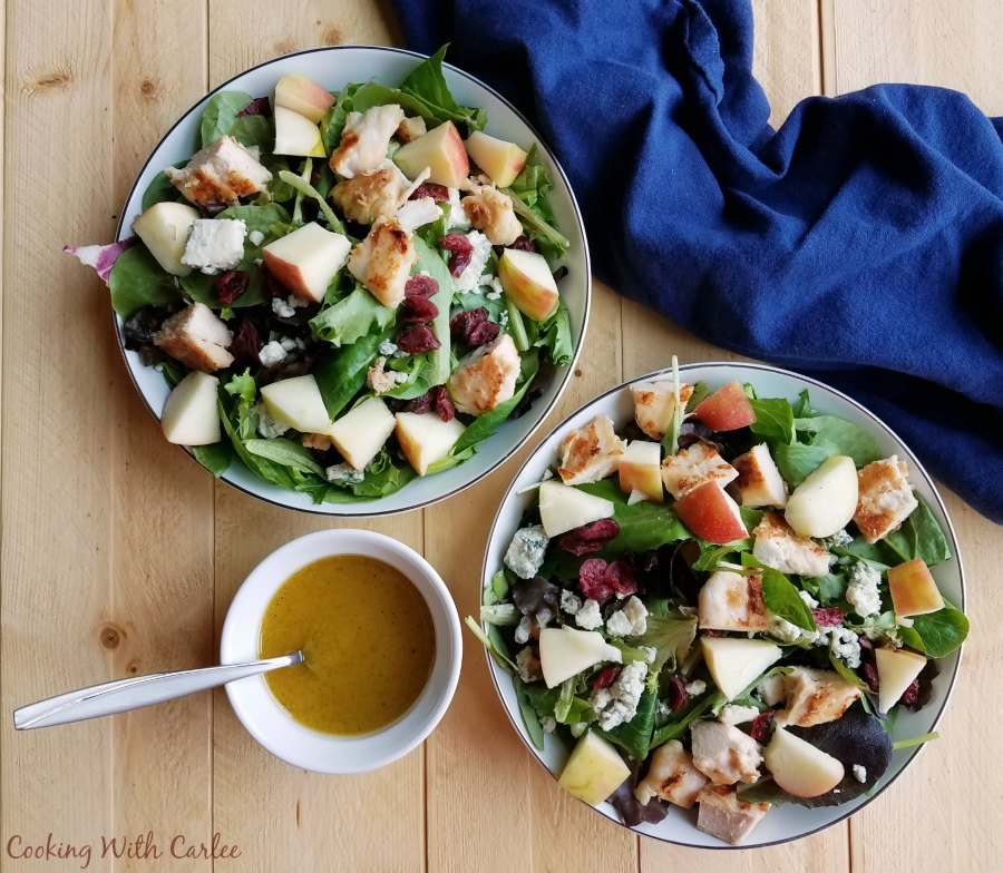 bowls of salad with chicken, cranberries, cheese, apples and homemade salad dressing