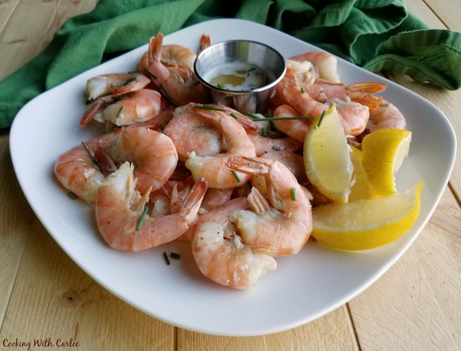 dinner plate filled with key lime roasted shrimp, lime butter and lemon wedges.