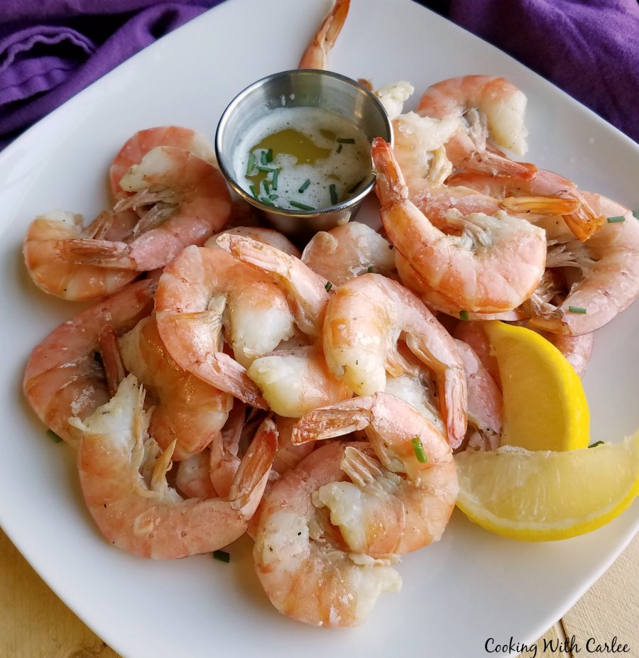 plate piled high with key lime roasted shrimp, a small container of lime butter for dipping and a couple of lemon wedges.