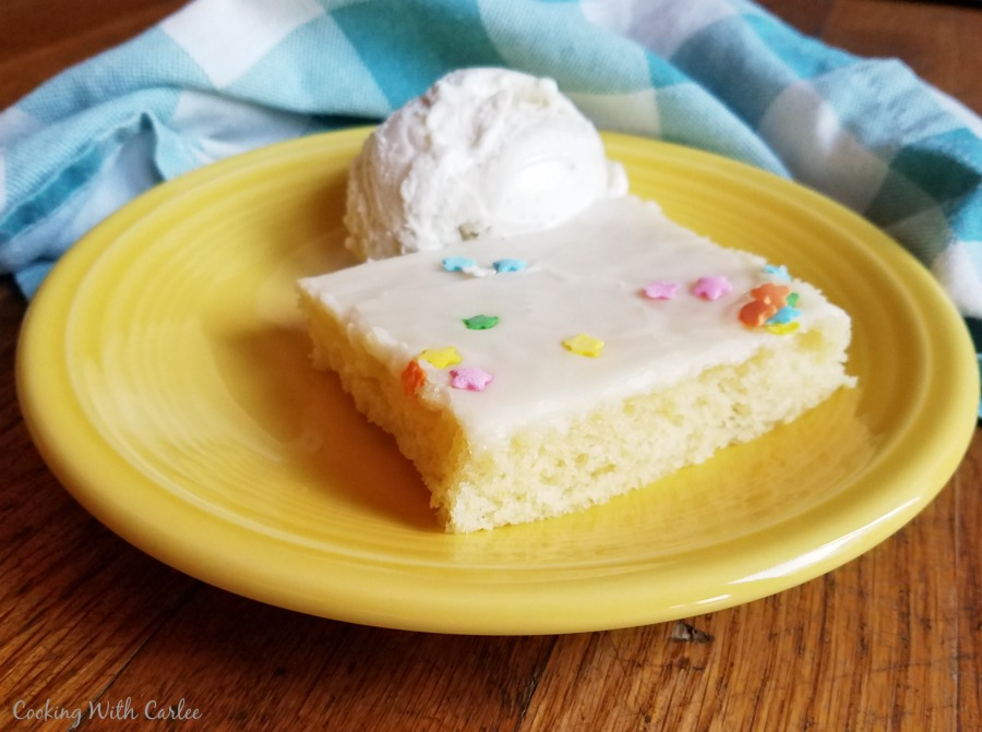 square piece of lemon cake on plate with scoop of ice cream