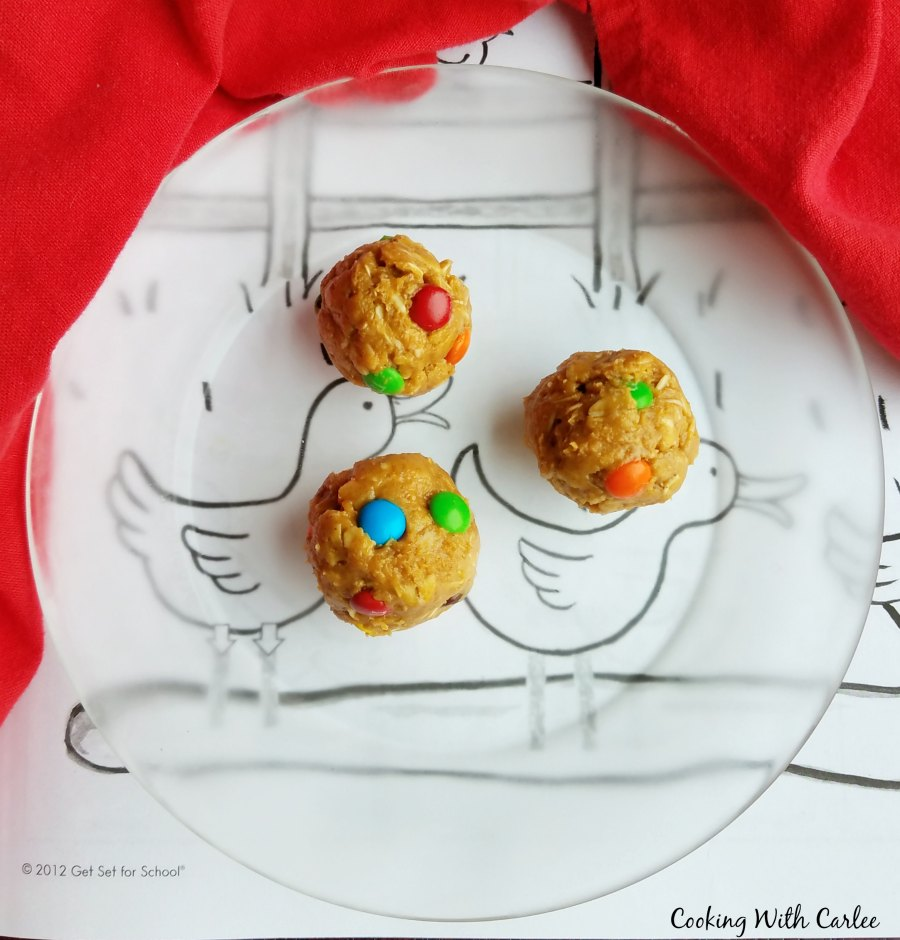 3 monster cookie dough balls on glass plate over coloring page.