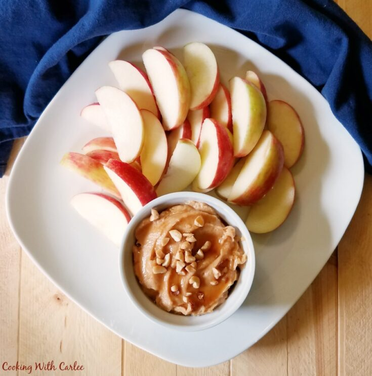 looking down at a plate of sliced apples and a ramekin of peanut butter yogurt fruit dip.