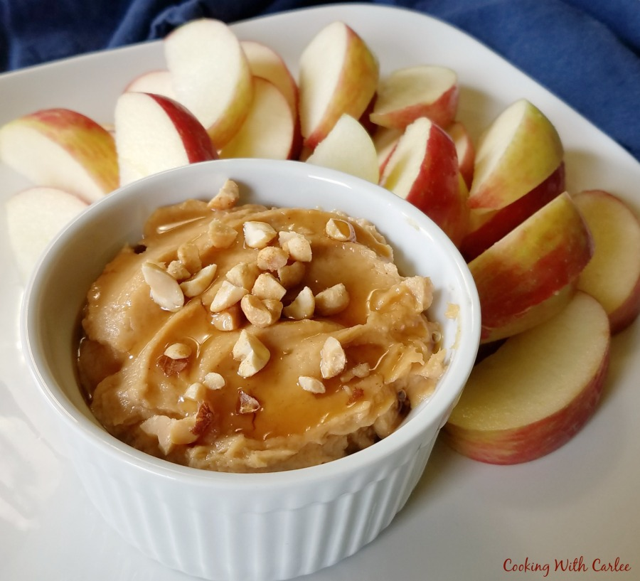 close up of ramekin filled with peanut butter yogurt dip with chopped peanuts and drizzle of honey on top and sliced apples on plate