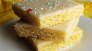 Stack of slices of lemon Texas sheet cake with smooth icing and sprinkles on top.