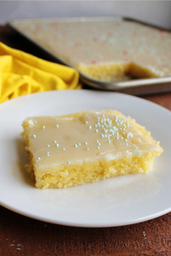 Piece of lemon Texas sheet cake with glossy icing and spinkles on top.