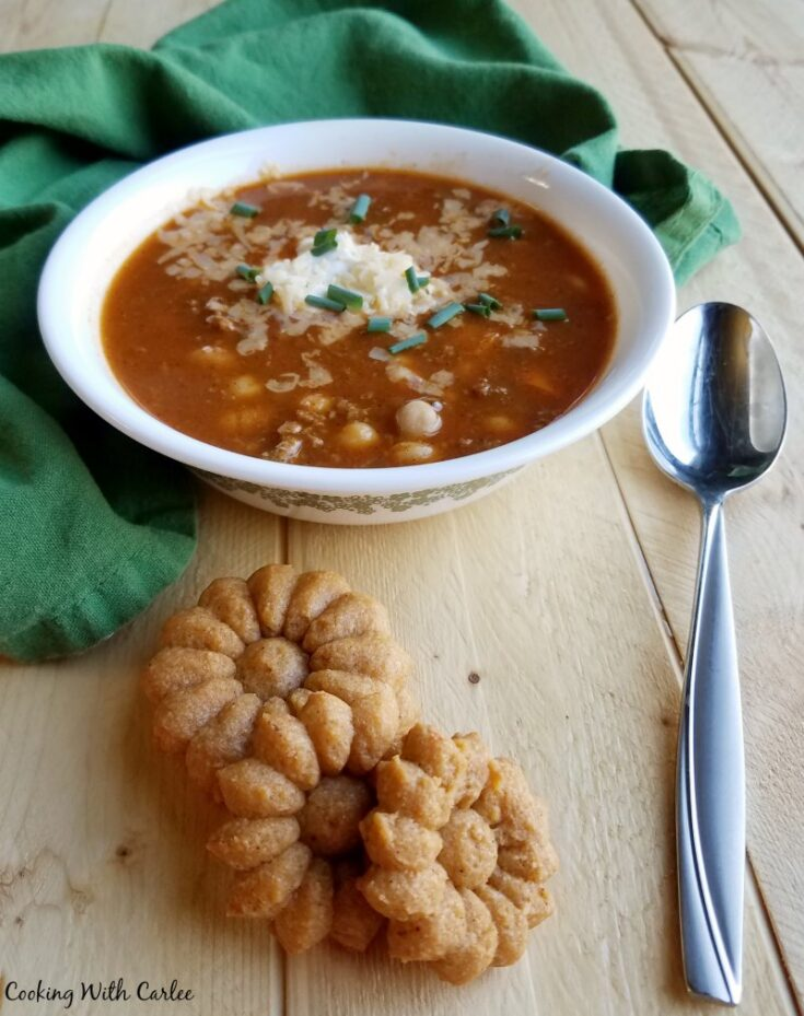 Bowl of chili topped with sour cream and cheese next to homemade flower shaped cheese crackers.