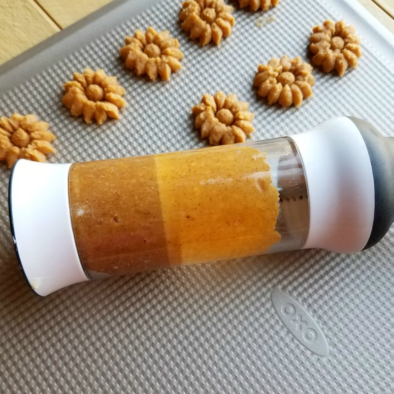cookie press filled with cracker dough and some crackers pressed out onto cookie sheet.