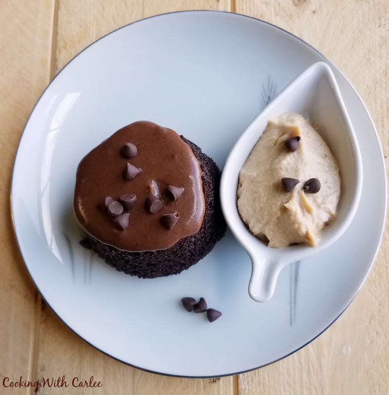 upside down chocolate cupcake with chocolate glaze, mini chocolate chips and a little leaf shaped bowl of peanut butter whipped cream.