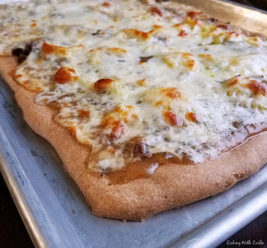 corner of freshly baked pizza on sheet pan.