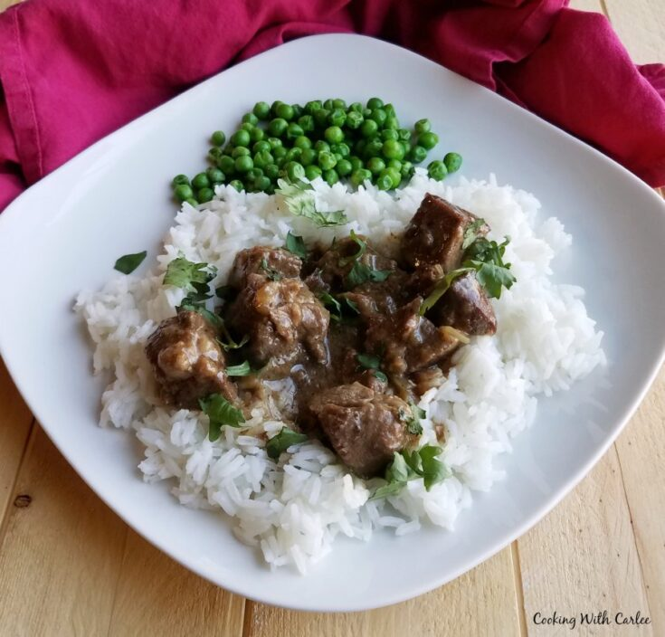 dinner plate with lamb curry and green peas.
