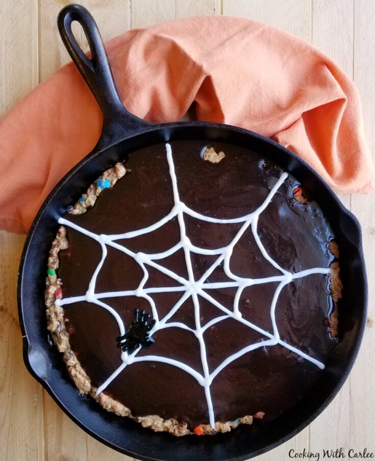 Cast iron skillet filled with large monster cookie topped with chocolate glaze with frosting spider web on top.
