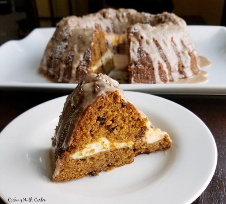 Slice of pumpkin chocolate chip bundt cake with ribbon of cream cheese down the middle.