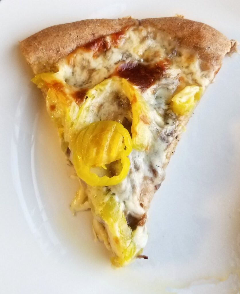 slice of Italian beef pizza with peppers and golden cheese ready to eat.