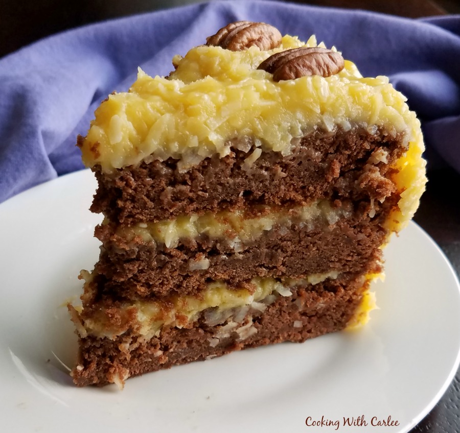 slice of three layer german chocolate cake with coconut frosting on dessert plate.