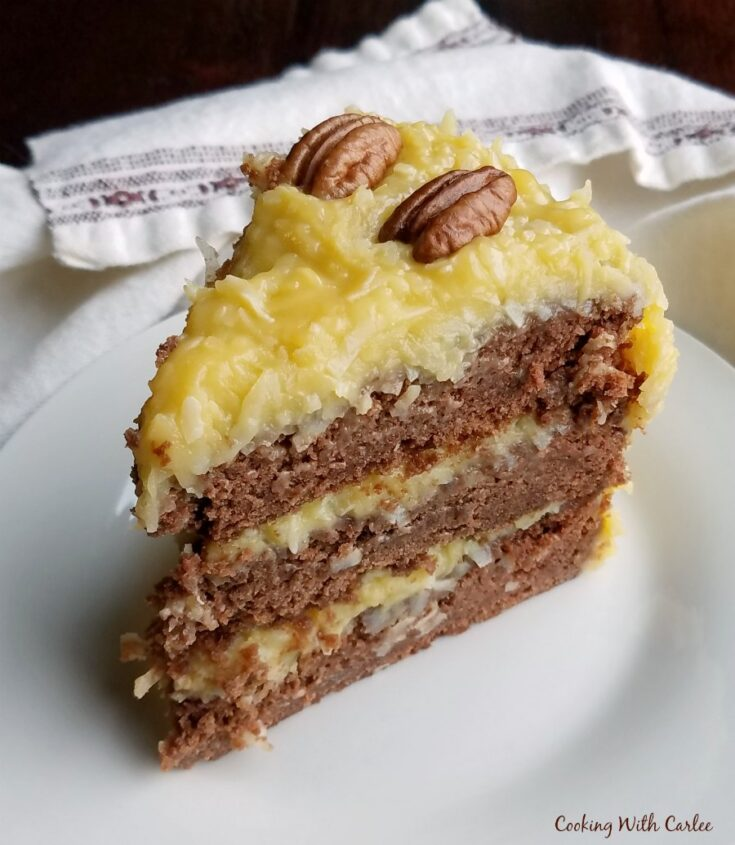slice of layered german chocolate cake with golden gooey coconut frosting.
