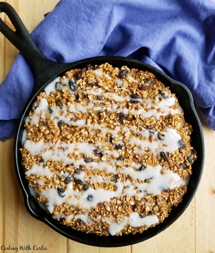 cast iron skillet filled with baked oatmeal drizzled with glaze.