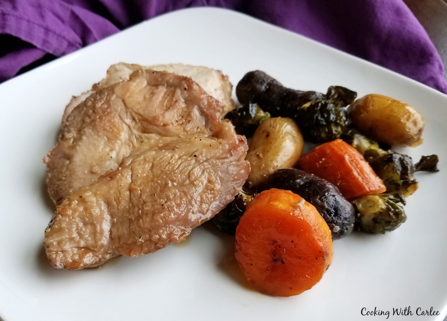 slices of pork and roasted veggies on plate