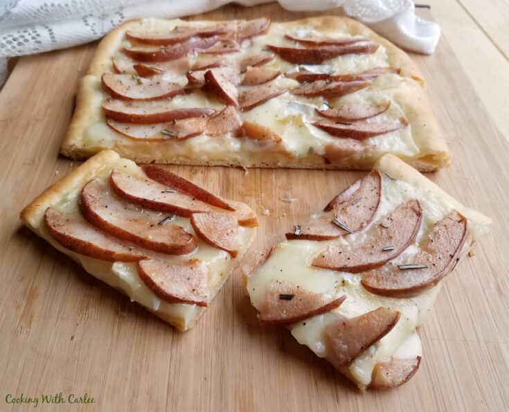 Slices of pear and brie flatbread on cutting board, ready to eat.