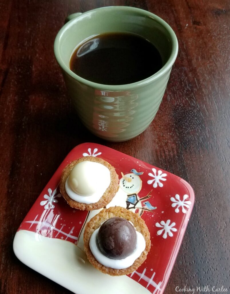 Small plate with a couple of cookie cups next to a mug of coffee.