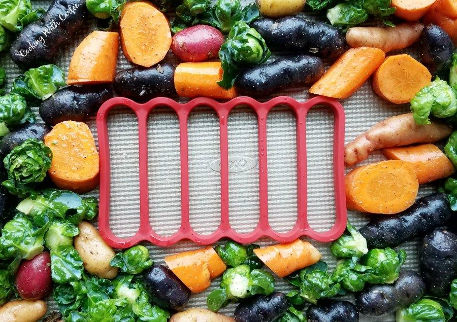 chopped veggies arranged abound roasting rack on sheet pan