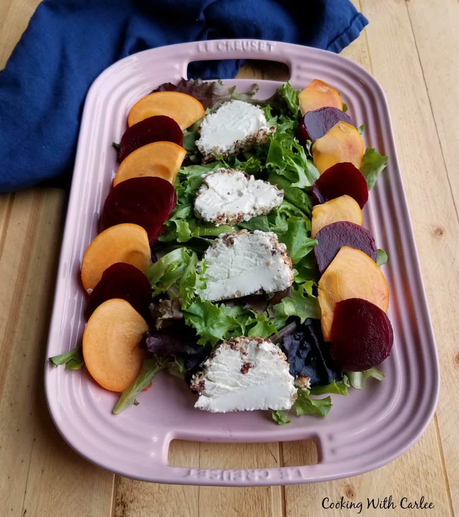 platter filled with salad topped with beets, persimmons and cheese.