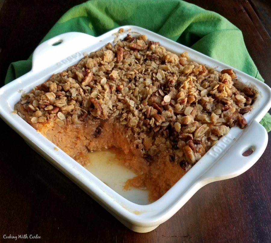 square dish filled with casserole with some missing showing the smooth sweet potato layer